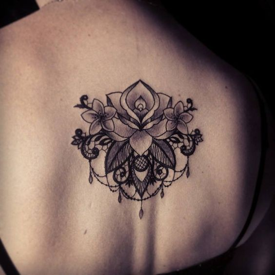 Large dot style back tattoo of large flowers by Caro Voodoo