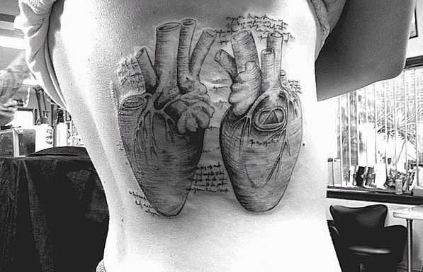 Large engraving style black ink side tattoo of human hearts and lettering