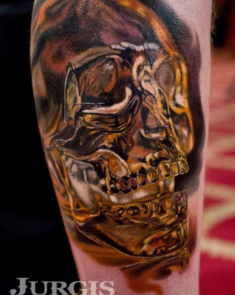 large gorgeous looking colored tattoo of golden skull