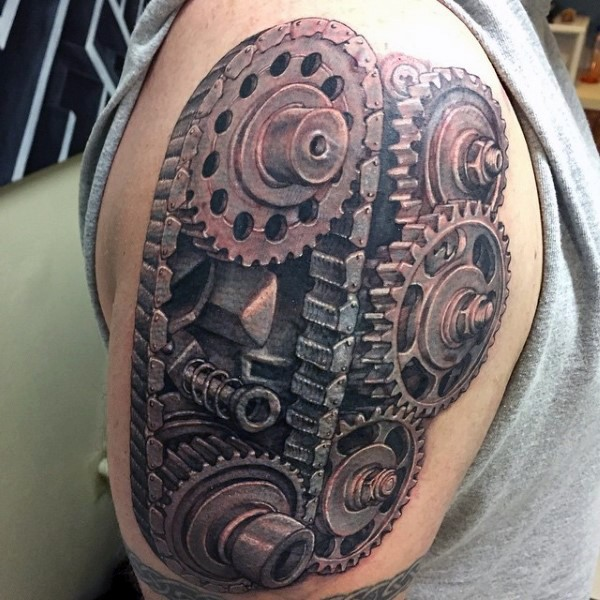 Large realism style engine gearwheels with chain tattoo on shoulder