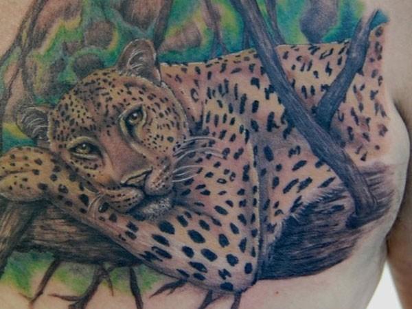 leopardo sdraiato sul albero tatuaggio sul petto