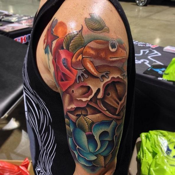 Lifelike beautiful looking shoulder tattoo of birds skull with frog and flowers