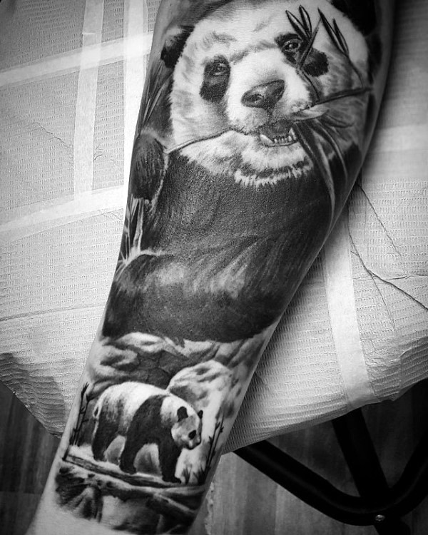 Lifelike breathtaking detailed forearm tattoo of cute panda bear eating grass