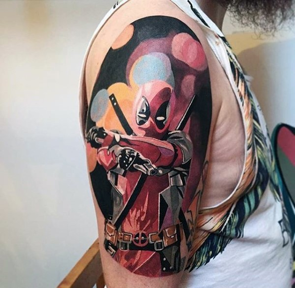 Lifelike colored Deadpool with pistols tattoo on shoulder