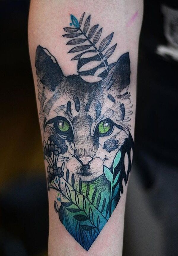 Lifelike nice looking painted by Joanna Swirska cat tattoo stylized with leaves