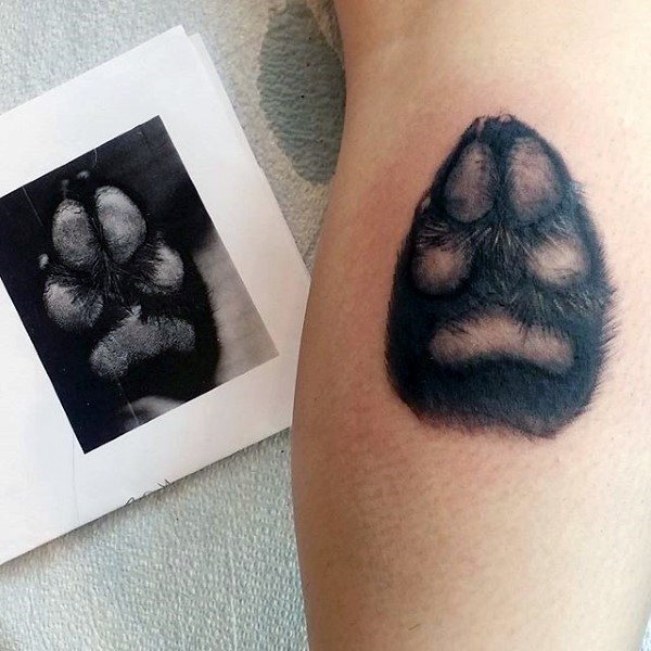 Lifelike very detailed tattoo of small dog paw