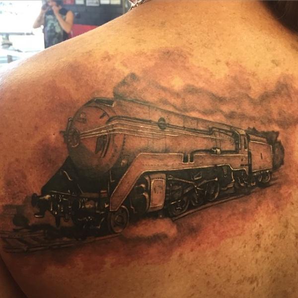 Lifelike very realistic upper arm tattoo of modern steam train