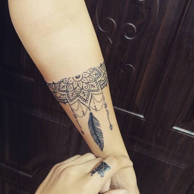 Linework style black ink forearm tattoo of floral ornament with feather