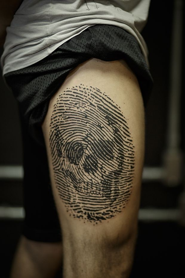 Linework style black ink thigh tattoo of finger print stylized with human skull