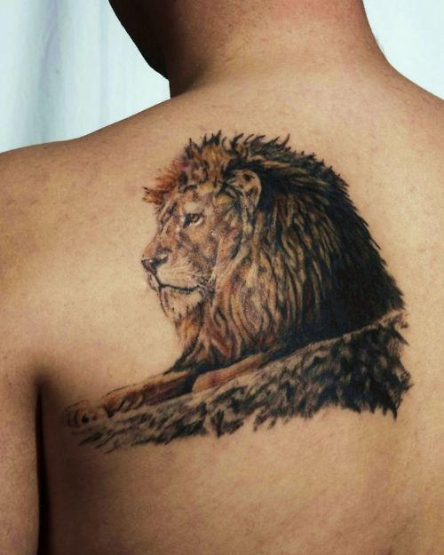 Lion face tattoo on tree on back