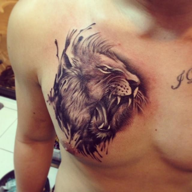 Lion head tattoo on the mans chest