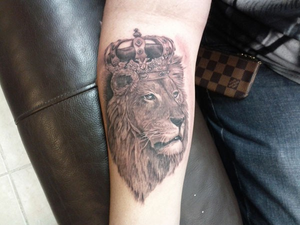 Lion in royal crown forearm tattoo