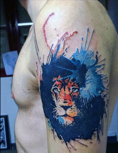 Lion&quots head multicolored watercolor shoulder tattoo with paint drips