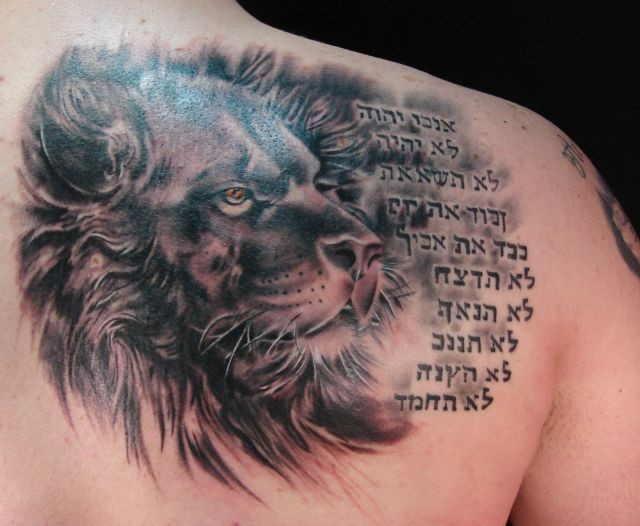 Lion head with hebrew writings tattoo