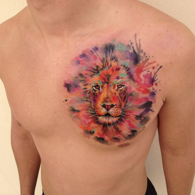 Lion&quots head with multicolored paint drips tattoo on chest in watercolor style