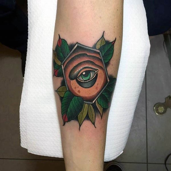 Little 3D like colored mystical eye in geometrical figure tattoo on forearm stylized with leaves