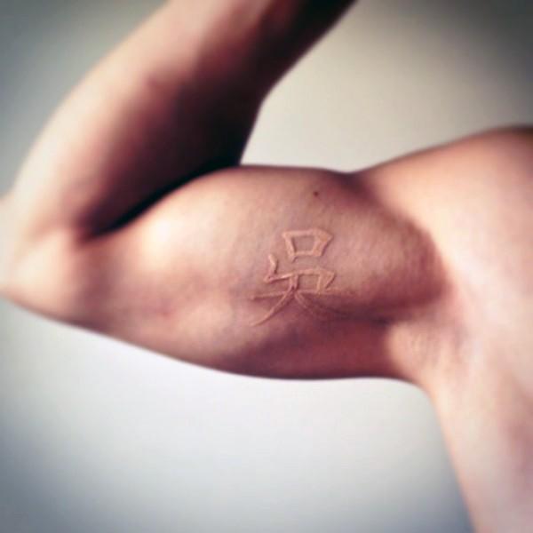 piccolo 3D inchiostro bianco simbolo Asiatico tatuaggio su bicipite