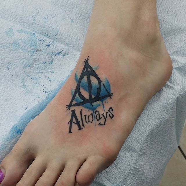 Little 3D style black ink mystical Harry Potter symbol tattoo on foot with lettering