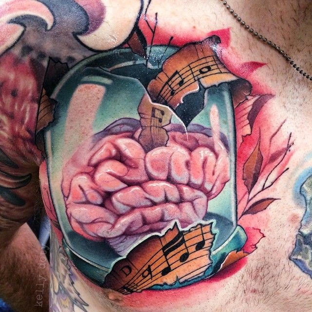 Little 3D style music themed human brain tattoo on chest combined with music notes