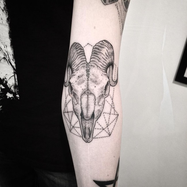 Little black and white animal skull tattoo on arm with geometrical ornaments