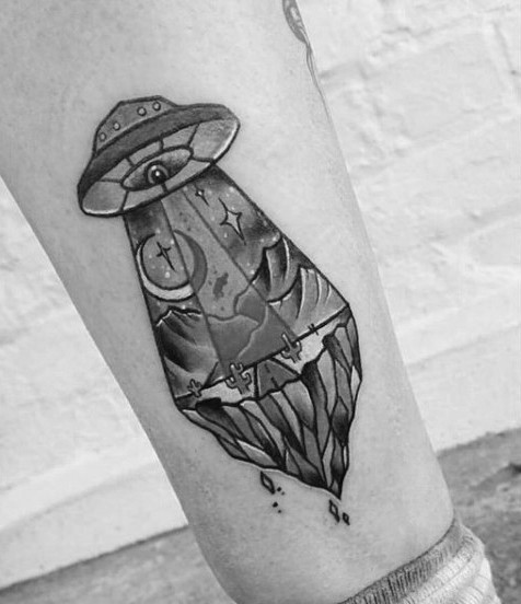 Little black and white cartoon like alien space ship tattoo on leg