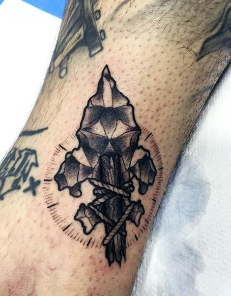 Little black and white detailed ancient spear head tattoo on leg
