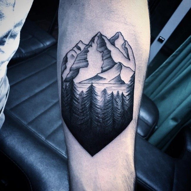 Little black and white forearm tattoo of mountain forest