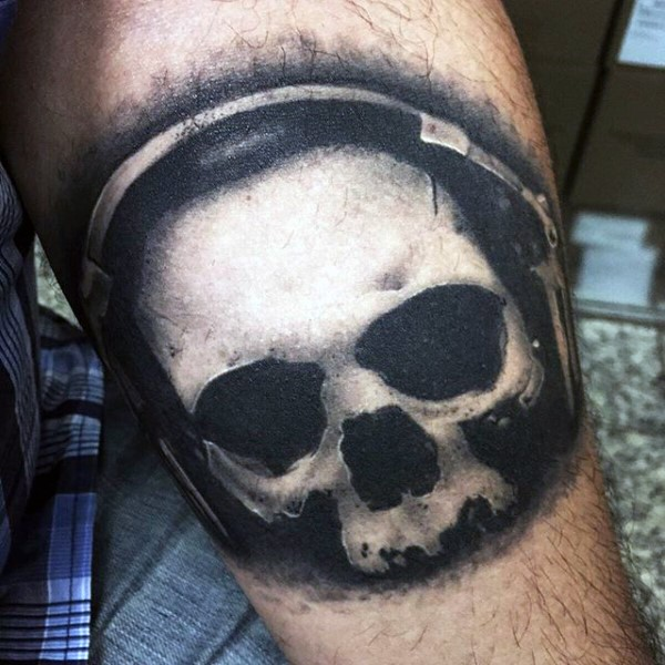 Little black and white skull with head set tattoo on arm