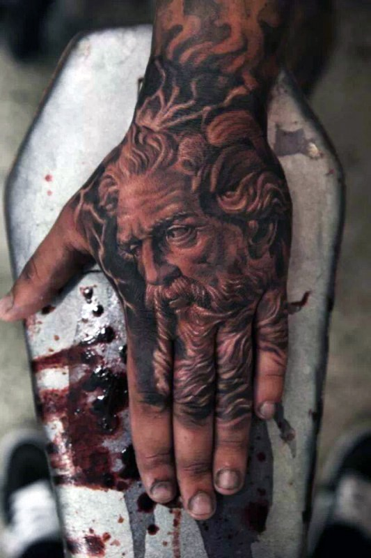 Little black ink detailed Poseidon face tattoo on hand