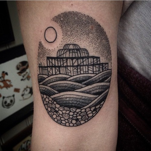 Little black ink oval shaped tattoo on arm stylized with sea pierce and moon