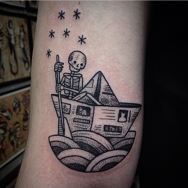 Little black ink paper ship with skeleton tattoo on arm stylized with stars