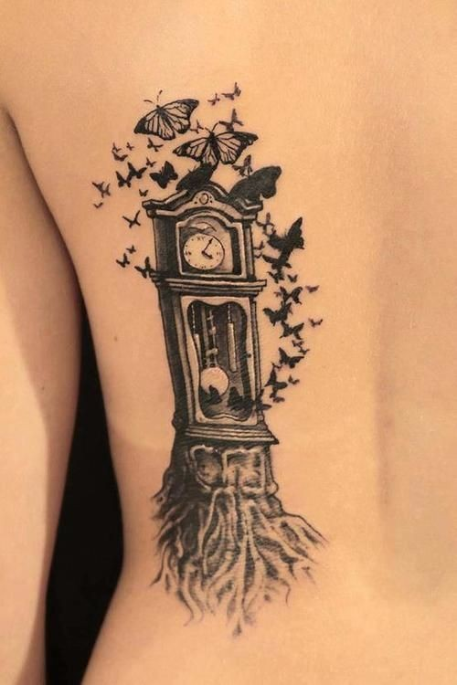 Little black ink tree shaped old clock tattoo on back with butterflies