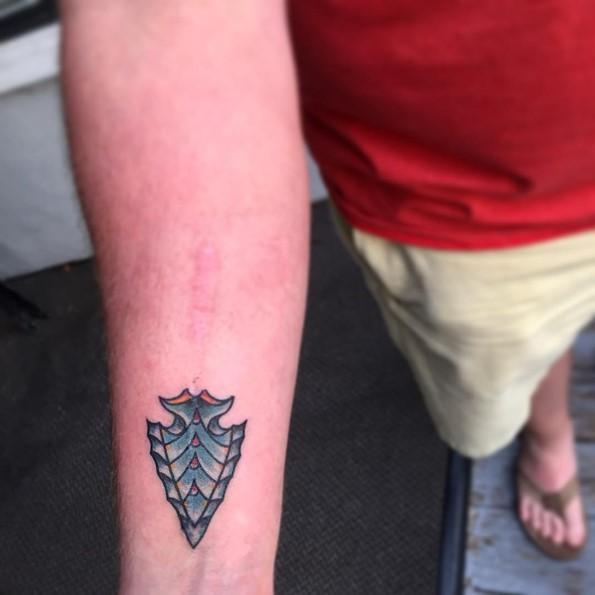 Little cartoon like colored antic forearm tattoo of tribal arrow head