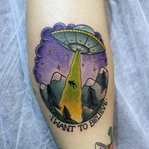 Little cartoon like colorful alien ship with human and lettering tattoo on leg