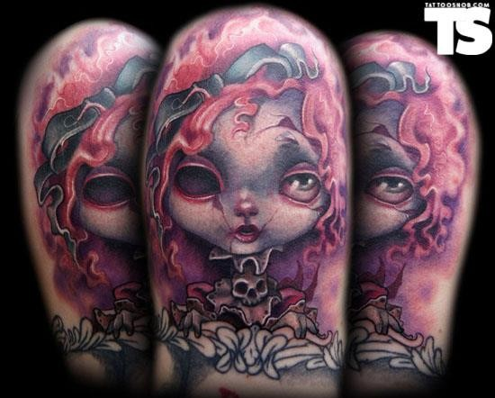 Little cartoon like strange evil doll tattoo on arm