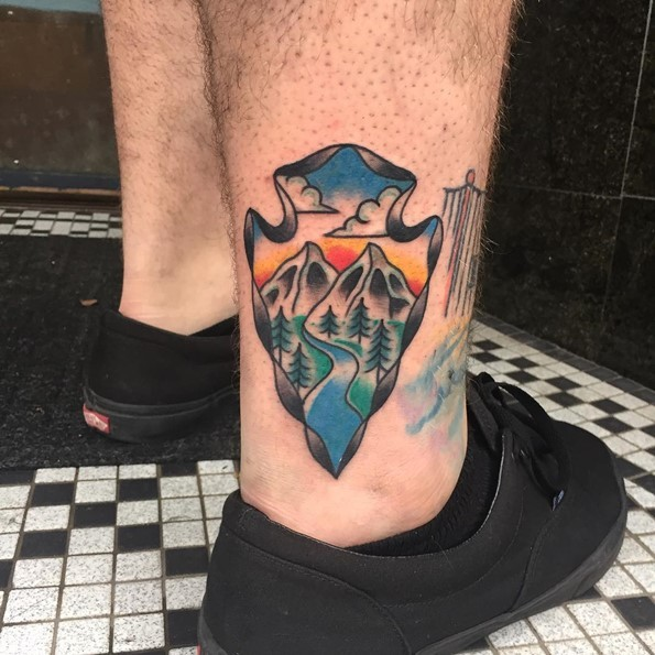Little cartoon style painted ancient weapon tattoo on ankle stylized with mountains