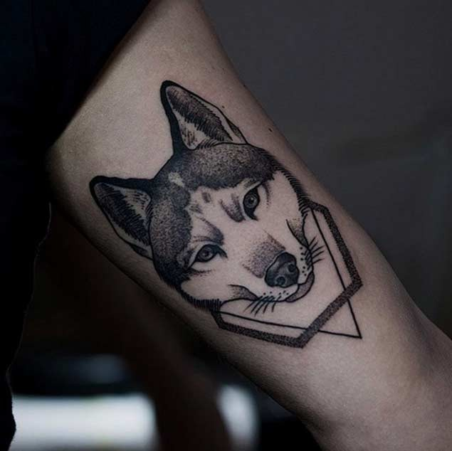 Little colored natural looking wolf head tattoo on arm with geometrical figure
