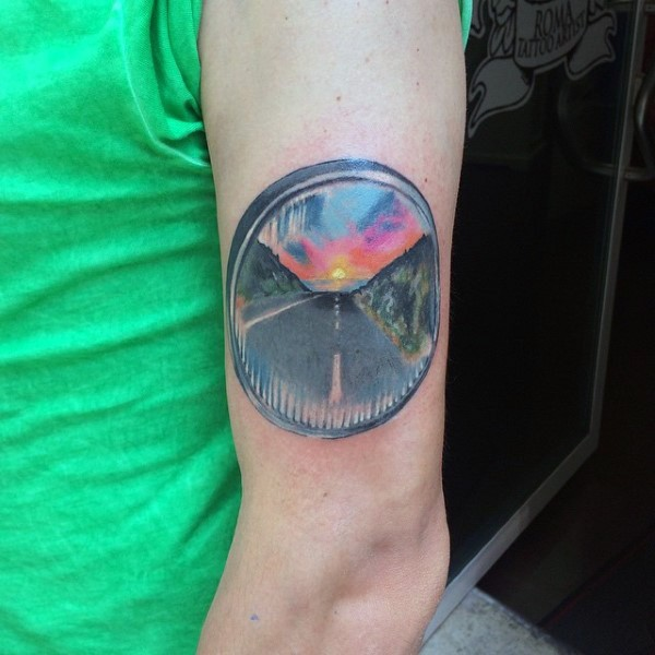 Little colored road with sunset tattoo on arm