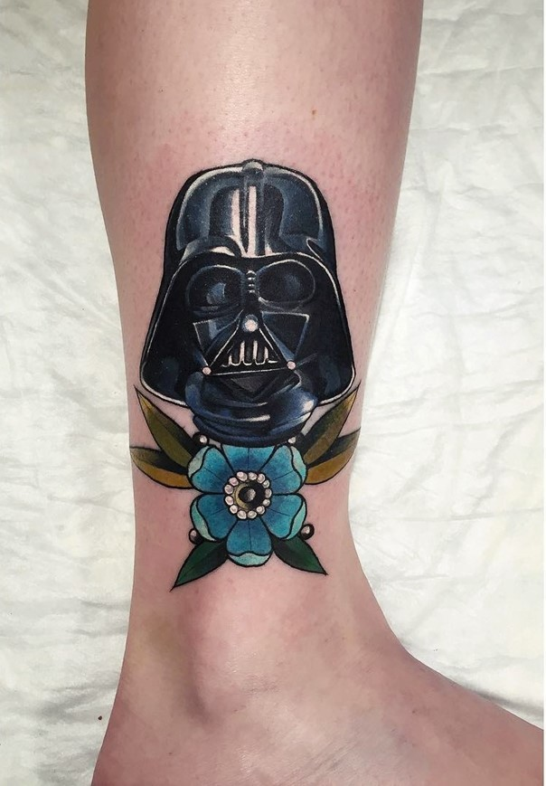 Little colorful detailed Darth Vaders mask tattoo on ankle stylized with beautiful flower