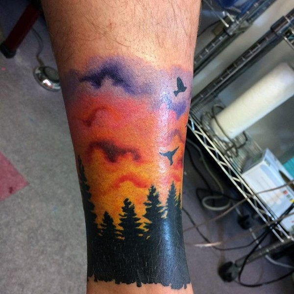 Little colorful sunrise above the forest tattoo on leg