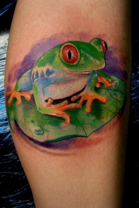 Little frog sitting on a green leaf tattoo