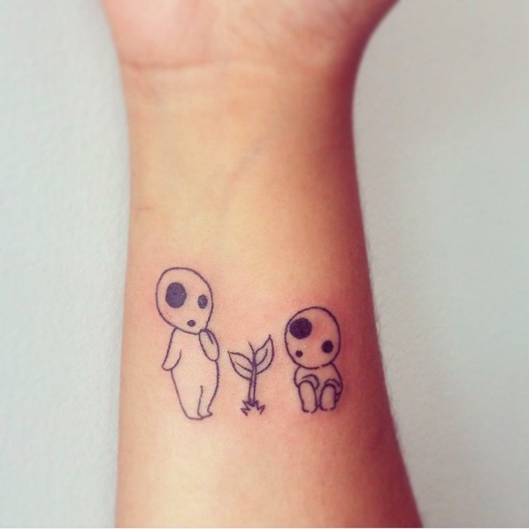 Little homemade black ink wrist tattoo of tiny monsters