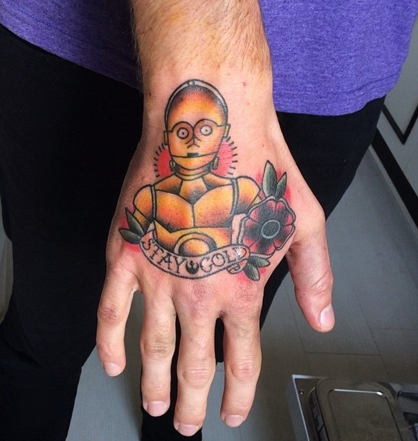 Little homemade like colored C3PO tattoo on hand stylized with flower and lettering