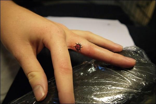 Tatuaje de mariquita diminuta en el dedo