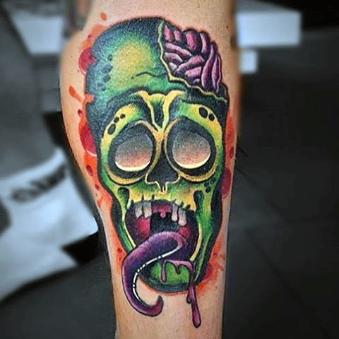 Little multicolored funny zombie head tattoo on leg muscle