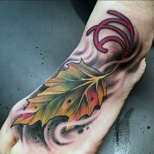 Little multicolored leaf with symbol tattoo on foot