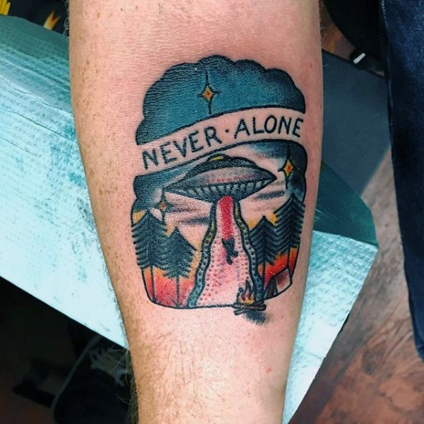 Little old school colored alien ship with human and lettering tattoo on arm