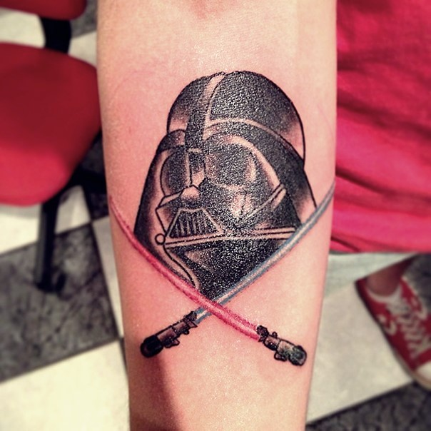 Little old school colored Darth Vader with crossed lightsabers tattoo on forearm