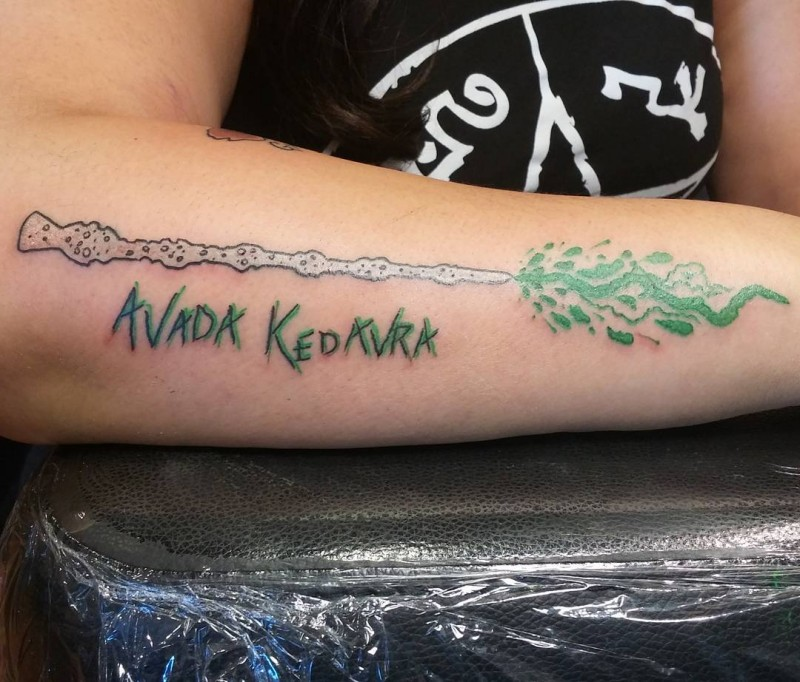 Little original colored magical wizard stick tattoo on forearm with spell lettering