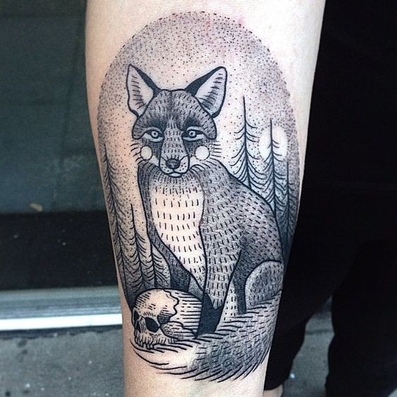 Little oval shaped black ink tattoo on forearm stylized with fox and human skull